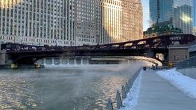 El vapor que sube y que sopla a través del río Chicago como temperaturas hunde en una mañana de congelación de enero en el lazo d almacen de video