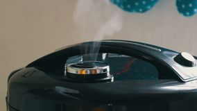 El vapor sale de la tapa del multicooker negro almacen de video