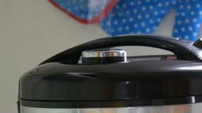 El vapor sale de la tapa del multicooker negro metrajes