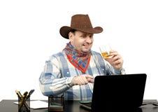El vaquero encontró algo divertido en Internet Foto de archivo