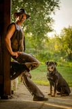 El vaquero se coloca con el perro en el granero Un hombre hermoso con un sombrero Fotografía de archivo