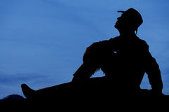El vaquero sienta puesta del sol mira para arriba Imágenes de archivo libres de regalías