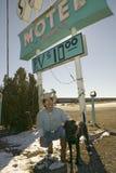 El vaquero y su perro se arrodillan abajo delante de la muestra del motel de las arenas con el estacionamiento de rv para $10, si Imagenes de archivo
