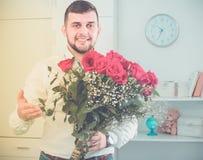 El varón 29-34 años está presentando las flores y el regalo Fotografía de archivo libre de regalías