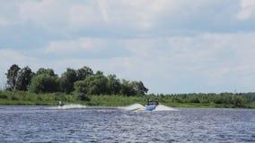 El varón activo está montando en waterski en el barco de siguiente de la superficie del agua a lo largo del río metrajes