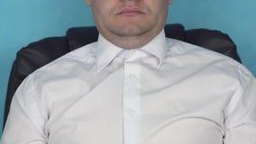 El varón adulto con la barbilla doble y vestido en camisa se sienta en la butaca Jefe o director gordo con la cara regordeta metrajes