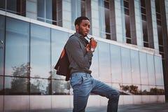 El varón afroamericano atractivo se está colocando cerca de su oficina fotos de archivo