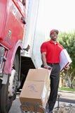 El varón afroamericano joven que se coloca con los paquetes acerca al camión de reparto fotos de archivo