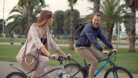 El varón alegre y los ciclistas femeninos están charlando feliz en caminar en parque de la ciudad almacen de video
