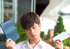El varón asiático decide y vacila para utilizar el dispositivo elegante Fotografía de archivo