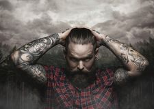 El varón barbudo brutal con el brazo tatuado mira abajo fotografía de archivo