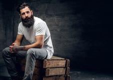 El varón barbudo con el tatuaje en el brazo vestido en una camiseta blanca se sienta imagenes de archivo