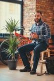 El varón barbudo hermoso del inconformista en una camisa azul y vaqueros del paño grueso y suave sostiene una taza de café de la  fotos de archivo