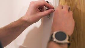 El varón blanco cierra una puerta de madera de la casa usando una cadena del interior almacen de metraje de vídeo