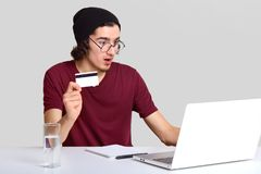 El varón chocado con apelar aspecto, sostiene la tarjeta plástica a disposición, siendo aterrorizado como cuenta bancaria de los  foto de archivo