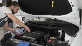 El varón comprueba el motor de coche del nivel de aceite de motor, examina visualmente color y la condición almacen de video