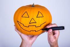 El varón da la calabaza del dibujo con el marcador para Halloween fotos de archivo libres de regalías