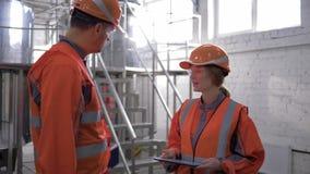 El varón de la igualdad de género en el trabajo, de los ingenieros de la fábrica y la hembra en cascos discuten nuevo proyecto y  metrajes