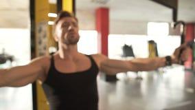 El varón de mediana edad del ajuste que hace entrenamiento pectoral de la mosca en el gimnasio, entrenando a su brazo muscles almacen de video