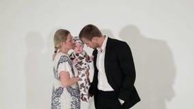 El varón de ojos azules maduro en traje se coloca al lado de la mujer que está deteniendo al bebé en manos almacen de video
