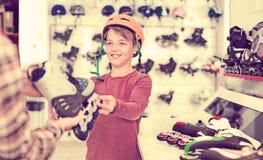 El varón de risa que demuestra patina sobre ruedas al muchacho Fotografía de archivo libre de regalías