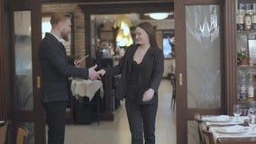 El varón del negocio y los socios comerciales femeninos se encuentran en el restaurante Gente que sacude las manos Señora en veni almacen de video