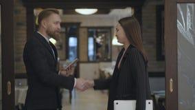 El varón del retrato y los socios comerciales femeninos se encuentran en el restaurante Gente que sacude las manos Se?ora en veni metrajes