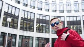 El varón dinámico en equipo y gafas de sol rojos del deporte canta al lado de columnas del granito almacen de video