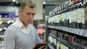 El varón elige el vino con una tableta almacen de video