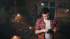El varón en el garaje casero en el fondo de estantes con las herramientas y las máquinas utiliza el calibrador almacen de video