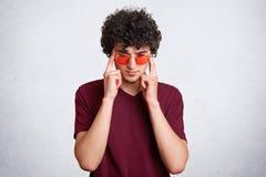 El varón enfocado pensativo con el pelo quebradizo, tiene expresión concentrada seria, lleva las gafas de sol rojas, aisladas sob Fotografía de archivo