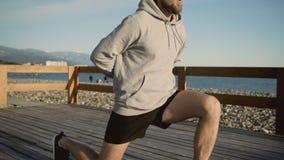 El varón está entrenando a sus piernas cerca del mar, haciendo posiciones en cuclillas con estocadas, primer almacen de video