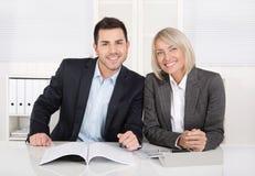 El varón feliz y el negocio femenino combinan sentarse en la oficina Succe Imagen de archivo