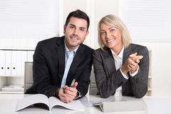 El varón feliz y el negocio femenino combinan sentarse en la oficina Succe Imagen de archivo libre de regalías