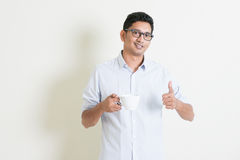 El varón indio del negocio casual bebe el café y el pulgar para arriba Foto de archivo libre de regalías