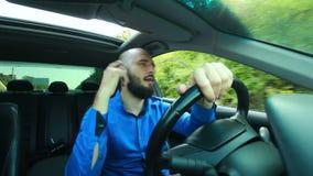 El varón joven con la barba canta y baila durante la conducción almacen de metraje de vídeo