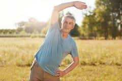 El varón maduro atlético con el cuerpo del ajuste, curvas a un lado, hace el ejercicio físico al aire libre, presenta contra fond imagenes de archivo