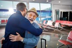 El varón mayor alegre está abrazando su cierre adulto del hijo Fotos de archivo