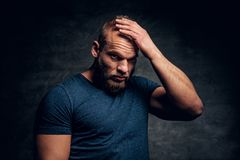 El varón muscular brutal vistió en un tacto azul de la camiseta su cabeza Imagenes de archivo