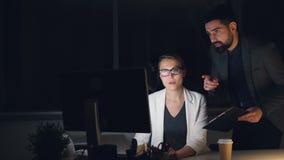 El varón ocupado de la gente joven y los colegas femeninos están trabajando en oficina en la noche que hablan y que miran la pant metrajes