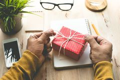 El varón que adorna la caja de regalo linda presenta en la mesa de trabajo Fotos de archivo libres de regalías