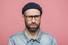 El varón sin afeitar del descontento infeliz mira con la expresión gruñona en cámara, lleva el sombrero negro y la camisa elegant imagenes de archivo