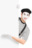 El varón sonriente imita al artista que muestra en un panel Imagen de archivo libre de regalías