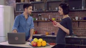 El varón y la muchacha disfrutan de la bebida caliente en el apartamento almacen de video