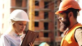 El varón y los ingenieros de sexo femenino controlan el proceso de la construcción Trabajadores en cascos en el área constructiva almacen de metraje de vídeo