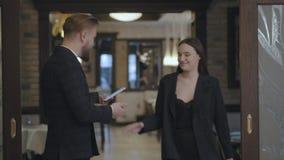 El var?n y los socios comerciales femeninos se encuentran en el restaurante Gente que sacude las manos Se?ora en un traje elegant almacen de video