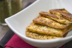El vegano sano frió rebanadas del queso de soja con los condimentos en la placa Foto de archivo libre de regalías