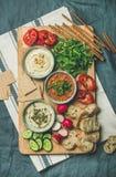 El vegetariano sumerge el hummus, babaganush, muhammara en el tablero de madera imagenes de archivo