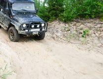El vehículo campo a través desliza abajo una cuesta arenosa, 4x4 Foto de archivo