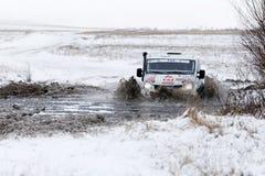 El vehículo de la reunión 4WD supera una charca mitad-congelada Fotos de archivo libres de regalías